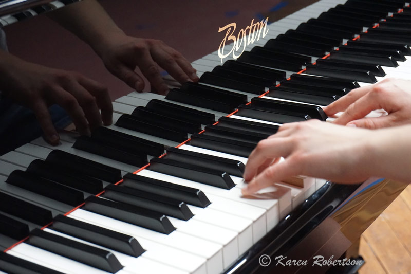 childs fingers on piano keyboard